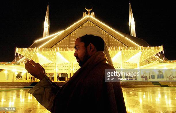 Pakistani Muslim man raises his hands in prayer on the night of AlQader in front of the illuminated Faisal Mosque in Islamabad 22 November 2003...