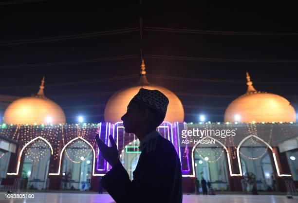 Pakistani Muslim prays at an illuminated mosque in connection with EideMiladunNabi the birthday of Prophet Mohammad in Karachi on November 20 2018...