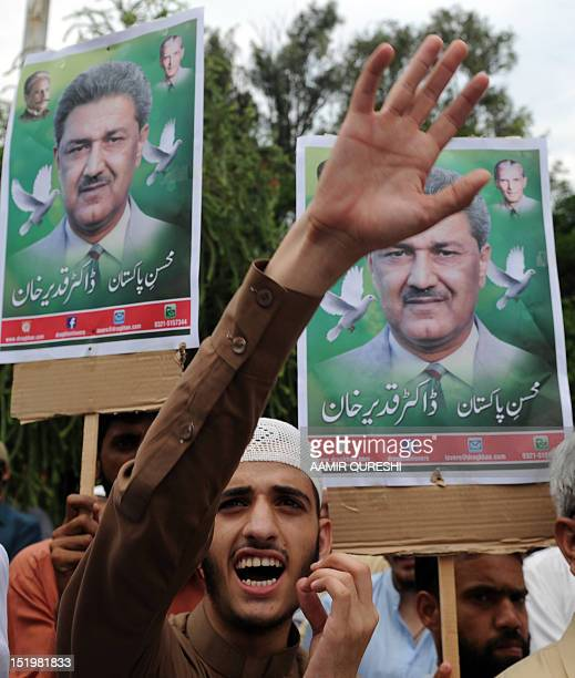 Pakistani Muslim protesters carry portraits of Abdul Qadeer Khan the father of Pakistan's nuclear bomb as they shout antiUS slogans during a...