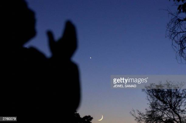 Pakistani Muslim raises his hands in prayer after viewing the new moon which announces the end of the Muslim holy month of Ramadan in Islamabad 25...
