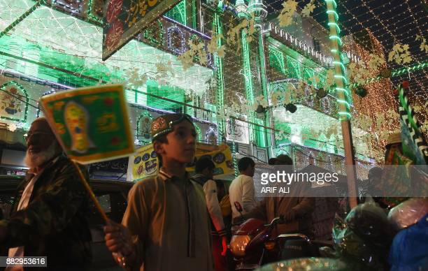 Pakistani Muslim walk through a street decorated with lights during celebrations marking EideMiladunNabi the birthday of Prophet Mohammad in Lahore...