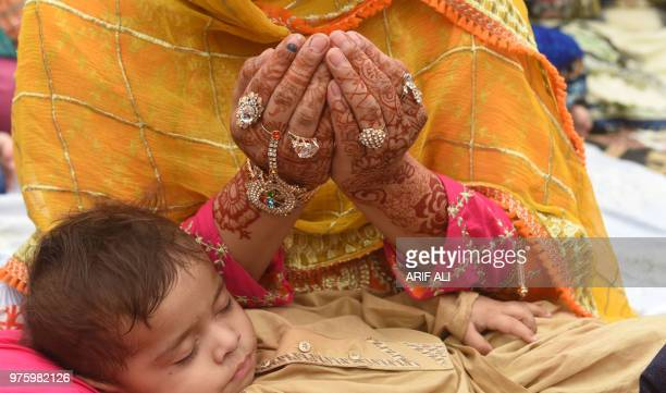 A Pakistani Muslim worshipper holds her child as she prays to mark Eid alFitr at the Badshahi Mosque in Lahore on June 16 2018 Muslims around the...