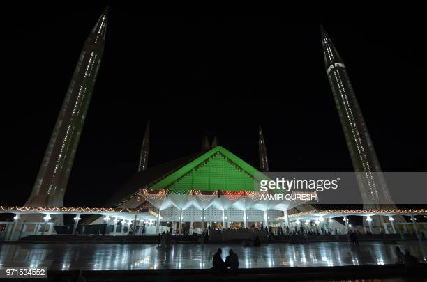 TOPSHOT Pakistani Muslim worshippers arrive for prayers at the illuminated Grand Faisal Mosque in Islamabad on the Lailat alQader also known as the...