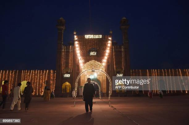 Pakistani Muslim worshippers arrive to the illuminated Badshahi Mosque in Lahore on June 22 2017 on Lailat alQader also known as the Night of Power...