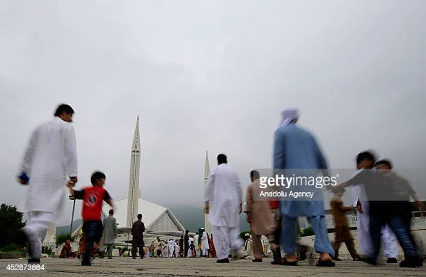 Pakistani muslims arrive at Faisal Mosque to perform Eid alFitr prayer in Islamabad Pakistan on July 29 2014