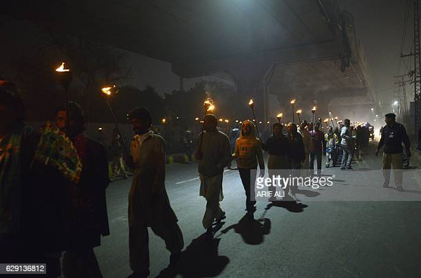 Pakistani Muslims carry burning lamps during celebrations on Mawlid alNabi the birth anniversary of Prophet Mohammed in Lahore on December 11 2016...