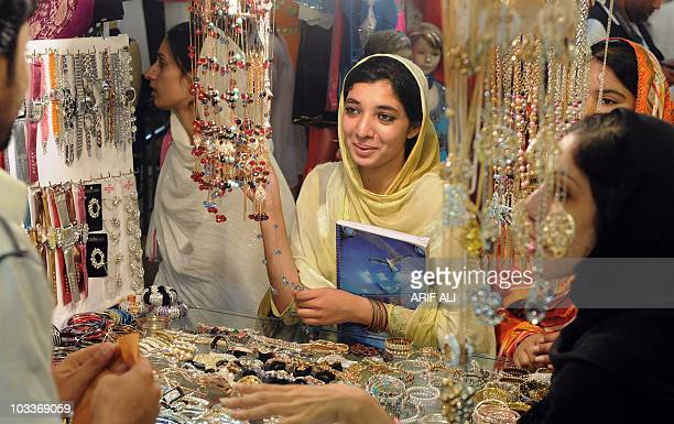 Pakistani Muslims choose jewellery at a stall in Lahore on September 17 ahead of the Eid alFitr Festival marking the end of the holy month of Ramadan...