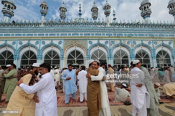 Pakistani Muslims exchange Eid greetings after performing Eid alFitr Prayer at Blue Mosque in Rawalpindi Pakistan on July 18 2015 Muslims around the...