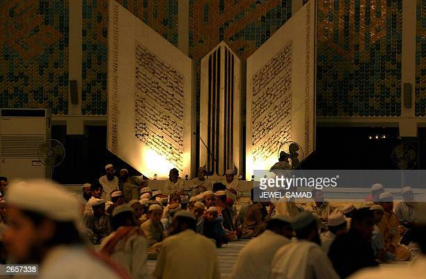 Pakistani Muslims gather for prayers in front of a huge mural of the Holy Koran at The Faisal Mosque in Islamabad 11 October 2003 Muslims worldwide...
