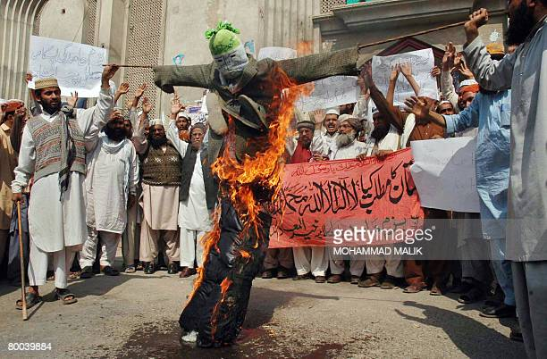 Pakistani Muslims hold a burning effigy of Danish prime minister Anders Fogh Rasmussen during a protest against the publication of drawings depicting...