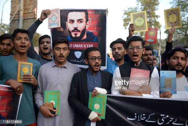 Pakistani Muslims hold Muslim Holy book Quran over the incident of desecration of the Quran in the Norwegian city of Kristiansand in Lahore on...