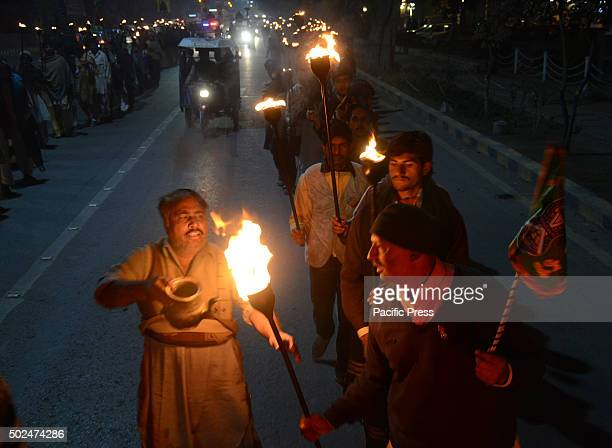Pakistani Muslims lights fireworks and carry burning torches during a procession celebrate the birthday of Prophet Mohammed in Lahore on December 23...