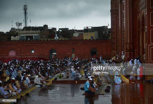 Pakistani Muslims offer congregational prayers despite of the rain in celebration of the Eid alFitr at the historical Badshahi Mosque in Lahore...