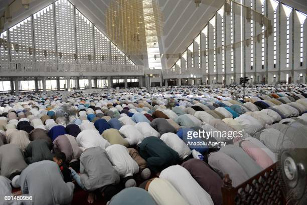 Pakistani Muslims perform the first Friday Prayer during Islam's holy fasting month of Ramadan at Turkishdesigned Faisal Mosque in Islamabad Pakistan...