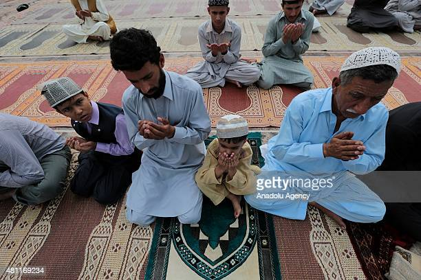 Pakistani Muslims raise their hands as they perform Eid alFitr Prayer at Blue Mosque in Rawalpindi Pakistan on July 18 2015 Muslims around the world...