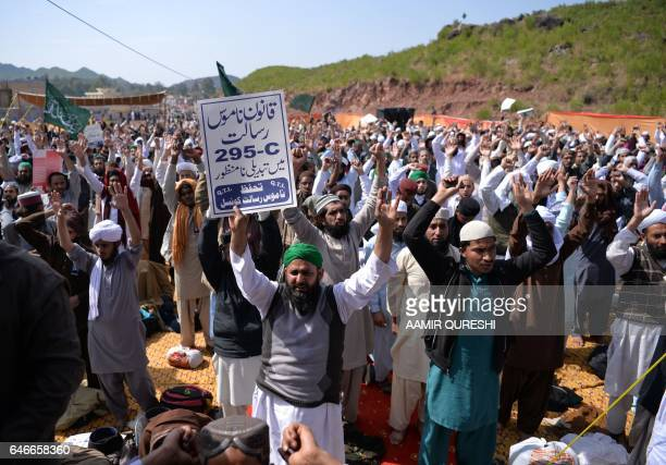 Pakistani Muslims raise their hands as they shout slogans as they gather outside the tomb of Mumtaz Qadri who was hanged in February 2016 for the...