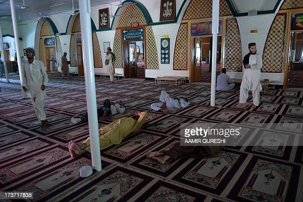 Pakistani Muslims rest after offering noon prayers at the Red mosque during the fasting month of Ramadan in Islamabad on July 17 2013 Islam's holy...