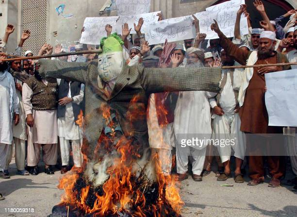 Pakistani Muslims shout slogans in front of a burning effigy of Danish prime minister Anders Fogh Rasmussen during a protest against the publication...