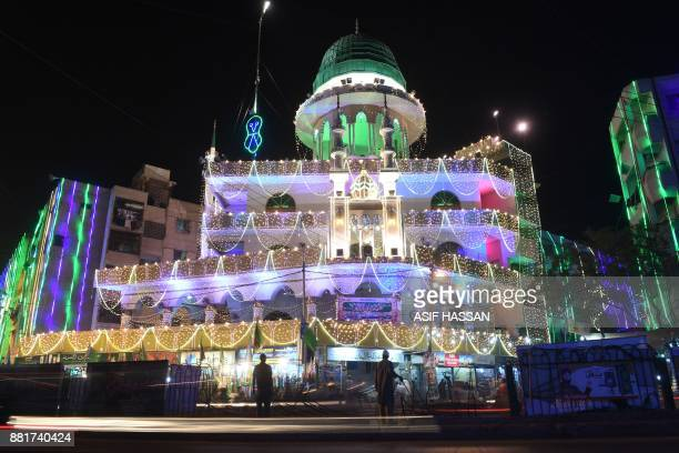Pakistani Muslims stand outside an illuminated mosque during celebrations marking the Eid MiladunNabi in Karachi on November 29 2017 Pakistani...