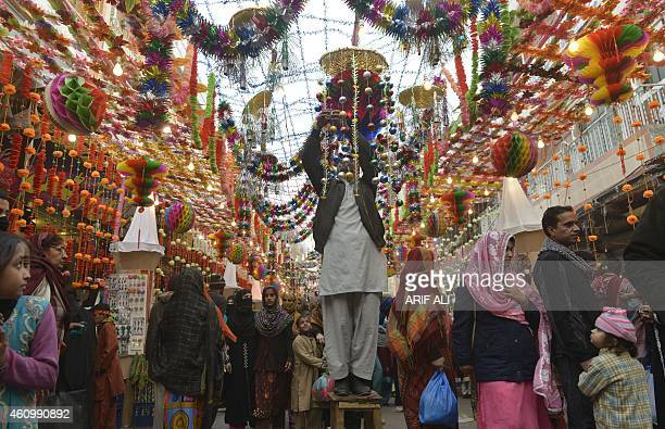 Pakistani Muslims walk in decorated market on the eve of the celebration of the birthday of Prophet Mohammed in Lahore on January 3 2015 The birthday...