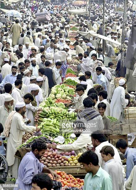 Pakistani Muslims walk through a busy market as they purchase food items to break their fast on the first day of the Muslim holy month of Ramadan in...