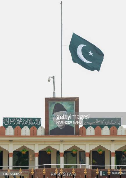A Pakistani national flag flies at halfmast over a picture of lawyer politician and the founder of Pakistan Muhammad Ali Jinnah on the Pakistani side...