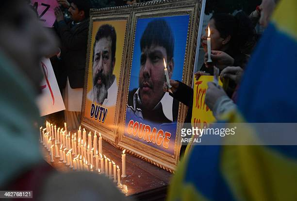 Pakistani NGO workers light candles in front of a portrait of slain police officer Chaudhry Aslam and Aitzaz Hassan a teenager who sacrificed his...