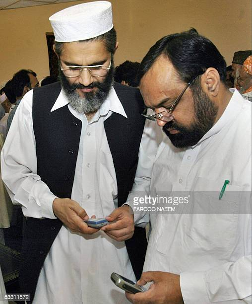 Pakistani NorthWest Frontier Province Finance Minister Sirajul Haq local government Minister Sardar Idrees check their cellular telephones as they...