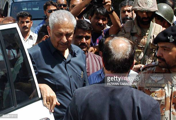 Pakistani nuclear scientist Abdul Qadeer Khan flanked by security personnel arrives at a mosque for funeral prayers for his deceased brother Abdul...
