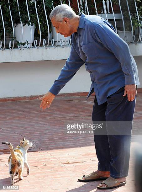 Pakistani nuclear scientist Abdul Qadeer Khan plays with his cat at his residence after a court verdict in Islamabad on February 6 2009 A Pakistani...