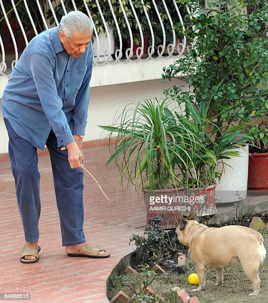 Pakistani nuclear scientist Abdul Qadeer Khan plays with his dog at his residence after a court verdict in Islamabad on February 6 2009 A Pakistani...