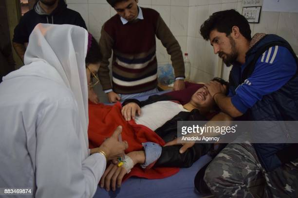 Pakistani nurse tends an injured victim at a hospital following an attack on Peshawar Agricultural Training Institute by Taliban militants in the...