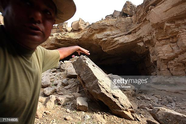 Pakistani officer shows a collapsed cave where the army says that the body of Baloch rebel leader Nawab Akbar Bugti lies beneath the rubble in the...