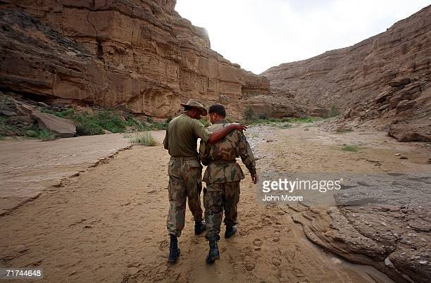 Pakistani officers congratulate each other while walking from a cave where the army says that the body of Baloch rebel leader Nawab Akbar Bugti lies...