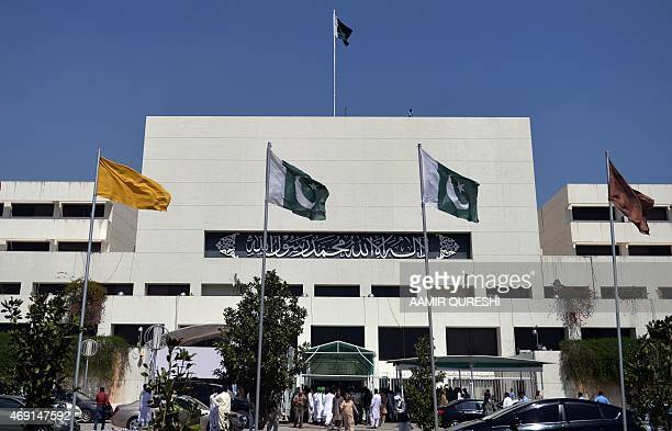 Pakistani officials and media personnel gather outside the parliament house building in Islamabad on April 10 2015 Pakistan's parliament on April 10...