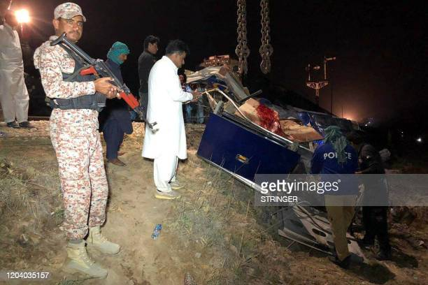 Pakistani officials remove the wreckage of a bus after a passenger train hit the bus in Sukkur on February 28, 2020. - At least 14 people were killed...