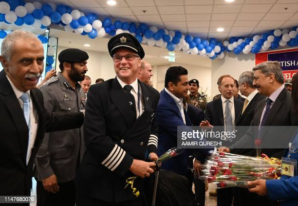 Pakistani officials welcome a British Airways pilot and passengers of the British Airways flight upon their arrival at the Islamabad International...