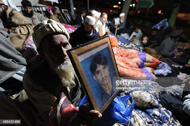 Pakistani old man holds a picture of his relative during a sitin protest in a camp set up by families of missing people at D Square outside the...
