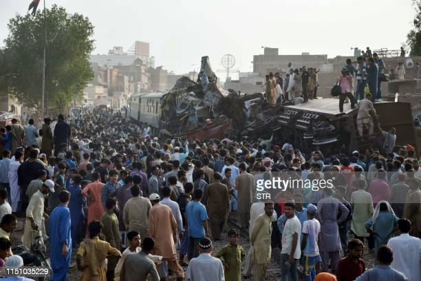 Pakistani onlookers gather around damaged carriages after a passenger train rammed into a goods train in Hyderabad on June 20 2019 At least three...