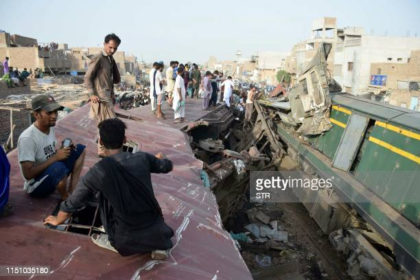 Pakistani onlookers stand a top a carriage after a passenger train rammed into a goods train in Hyderabad on June 20 2019 At least three people were...
