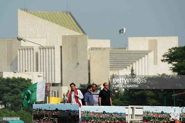 Pakistani opposition politician Imran Khan addresses supporters as the Supreme Court building is pictured in the background in Islamabad on August 21...