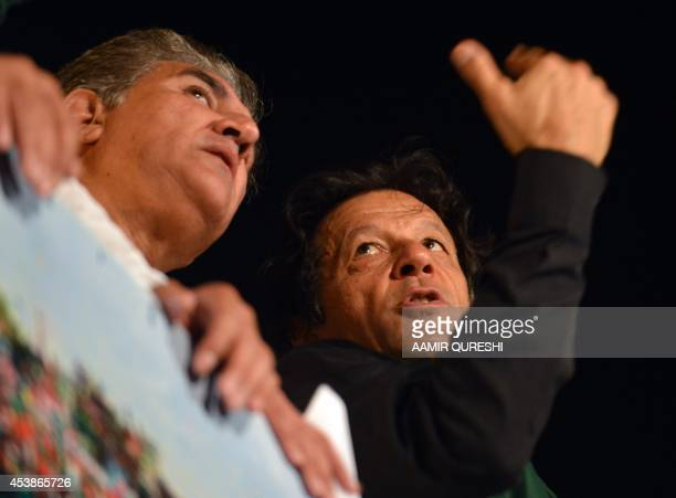 Pakistani opposition politician Imran Khan speaks with party vice chairman Shah Mehmood as he attending a protest in front of Parliament in Islamabad...