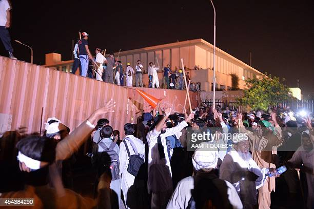 Pakistani opposition protesters climb on shipping containers used as a barricade to march towards the prime minister's residence in Islamabad on...
