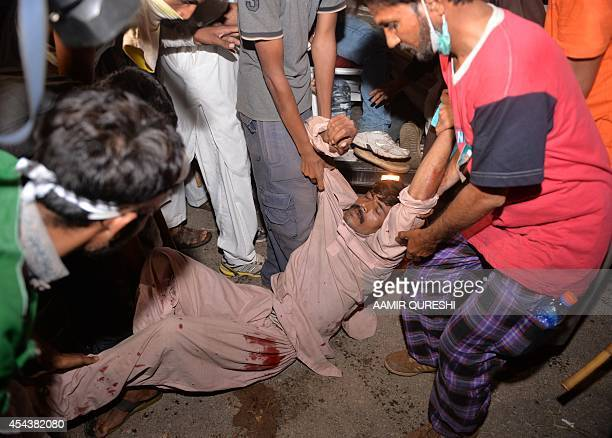 Pakistani opposition supporters carry a wounded protester following clashes with security forces near the prime minister's residence in Islamabad on...
