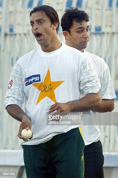Pakistani pace bowler Shoaib Akhtar yawns as his teammate Azhar Mahmood looks on during a practice session on the eve of the fifth One Day...