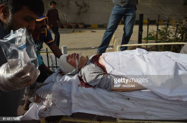 Pakistani paramedics push a stretcher carrying an injured Chinese national to an hospital after an attack by gunmen in Karachi on February 5 2018...