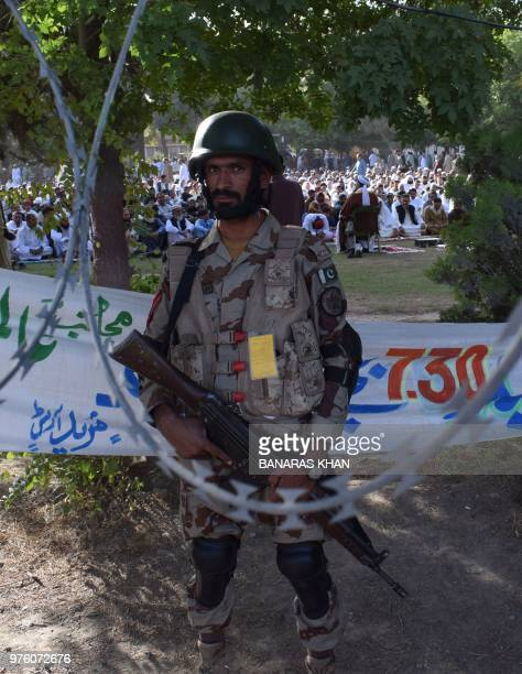 A Pakistani paramilitary soldier stands gaurd as Muslim offer Eid alFitr prayers in Quetta on June 16 2018 Muslims around the world are celebrating...