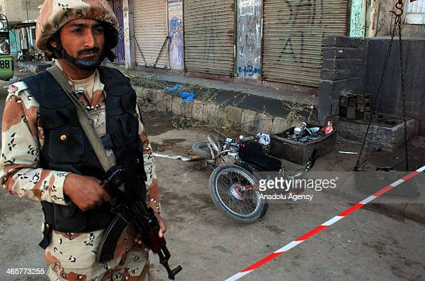 Pakistani paramilitary soldier stands guard around the site of a suicide bomb attack near Rangers' checkpost in Karachi January 29 2014 Three bomb...