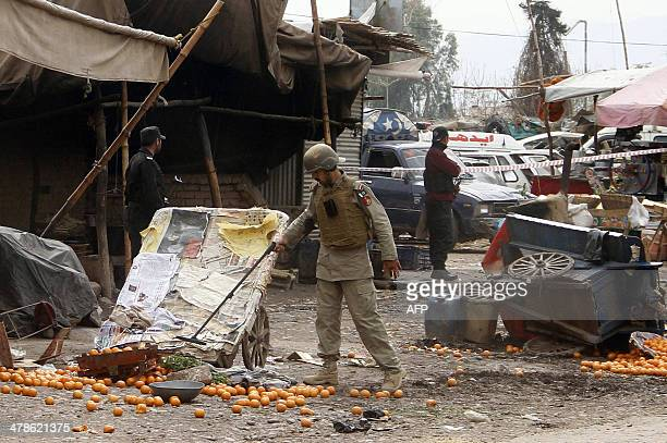 A Pakistani paramilitary soldier uses a metal detector at the site of a suicide attack on the outskirts of Peshawar on March 14 2014 A suicide bomb...