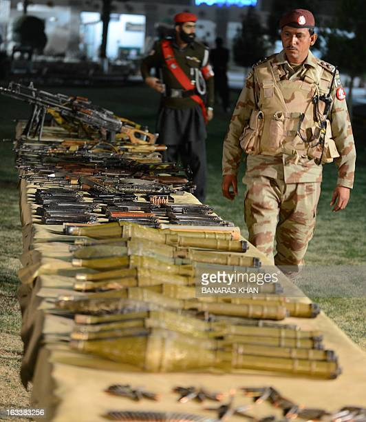 A Pakistani paramilitary soldier walks beside seized weapons displayed at a security compound in Quetta late March 8 2013 Pakistani paramilitary...